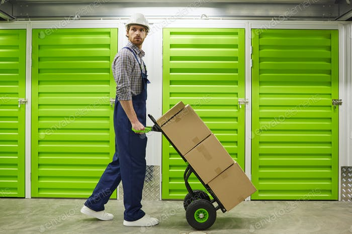 Worker carrying cart in warehouse
