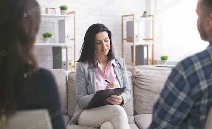 Professionelle Psychologe nimmt Notizen bei Paartreffen mit Patienten
