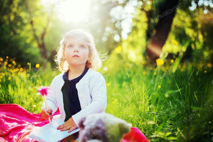 Happy little girl in a summer picnic at the park.
