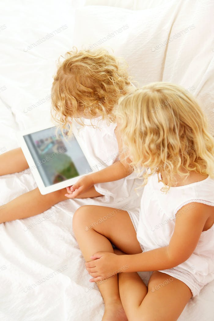 Two little girls using digital tablet on bed