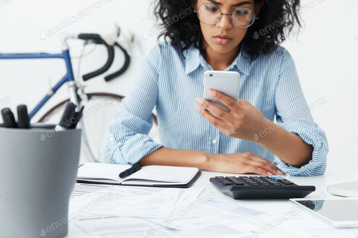 Serious young female employee in stylish glasses sitting at her desk and using mobile phone, looking