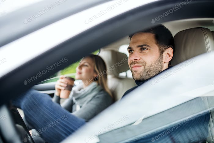 Happy young couple with coffee sitting in car, driving.