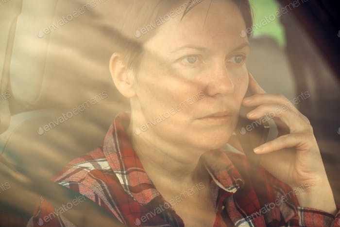 Worried woman talking on mobile phone in car
