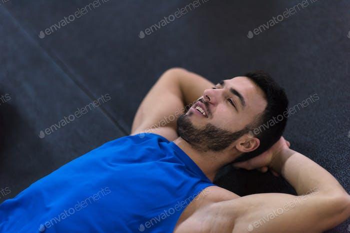 junger Sportler auf dem Boden liegend und entspannend