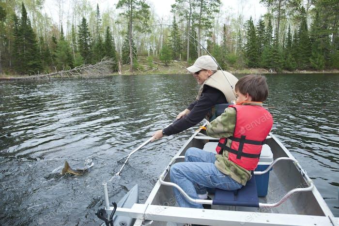 Junge und Vater Angeln in einem Kanu