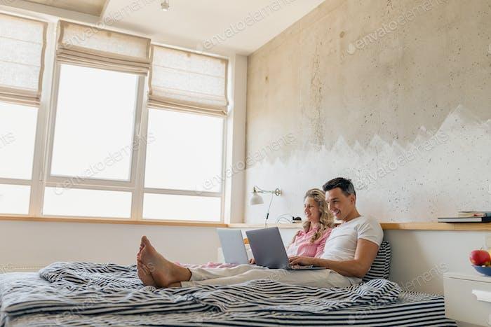 junges attraktives Paar sitzt morgens auf dem Bett, Online-Freelancer-Job
