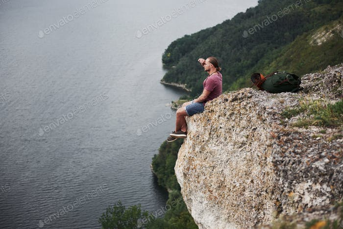 Attractive man enjoying the view of the mountains landscape above the water surface