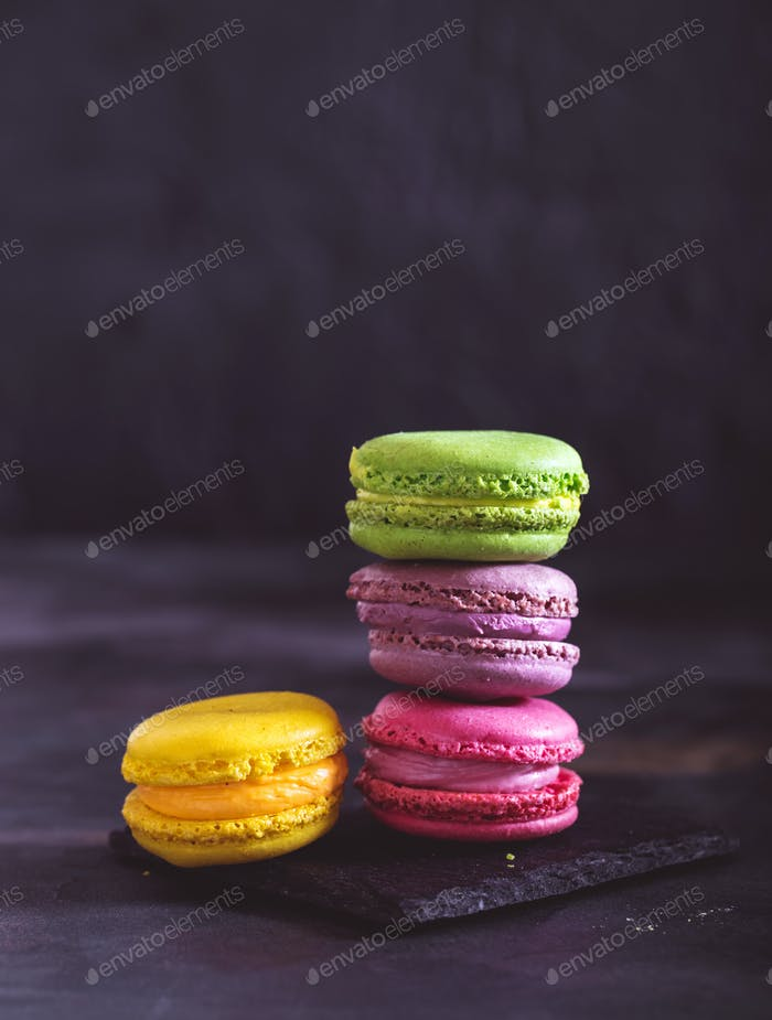 Colorful French macaroons on dark background