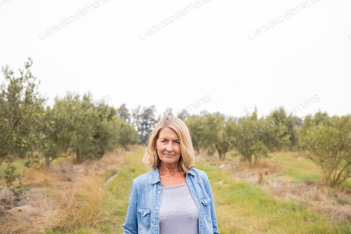 Happy woman standing in olive farm