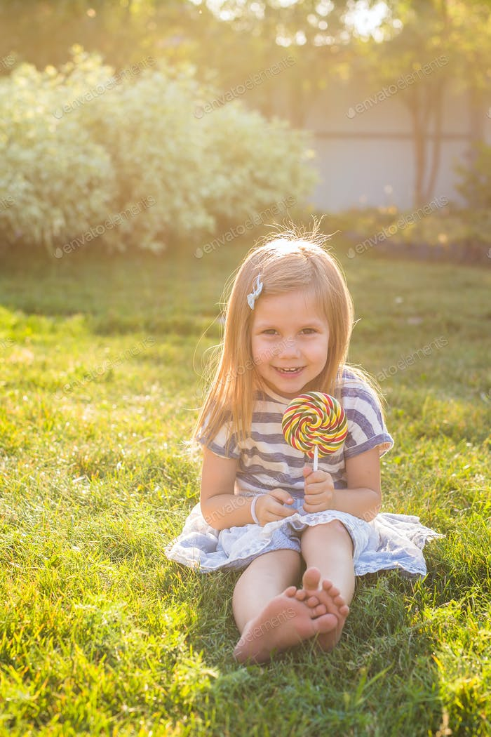 Funny child with candy lollipop, happy little girl eating big sugar lollipop, kid eat sweets