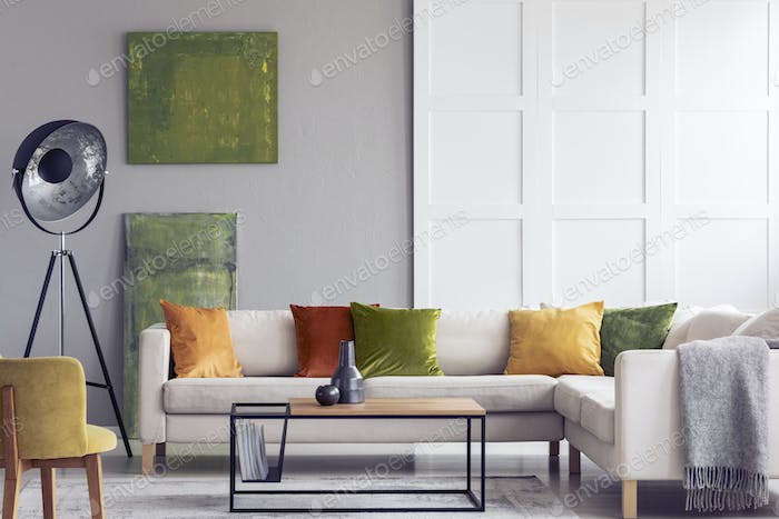 Yellow and green pillows on white settee in living room interior