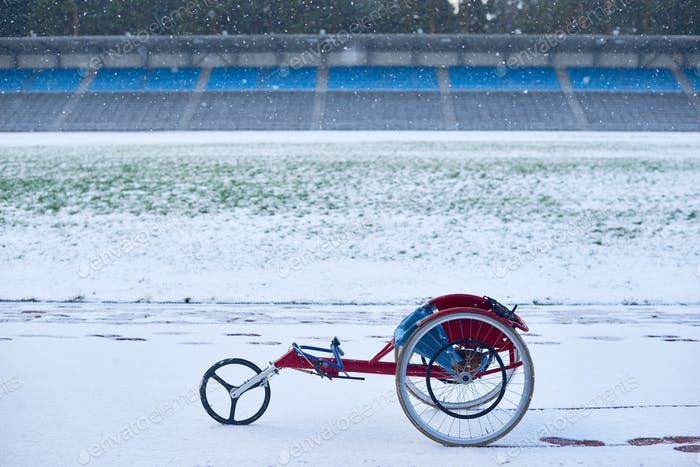 Modern racing wheelchair standing at outdoor track and field stadium