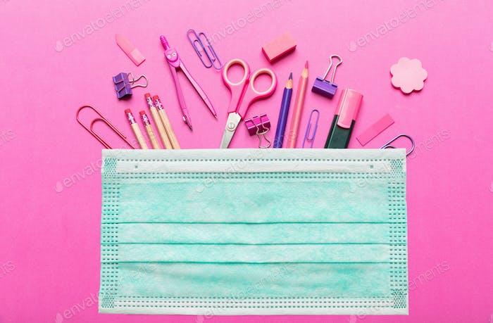 Chirurgische Maske und Schulbedarf auf rosa Hintergrund. Coronavirus-Ausbreitung Präventionsmaßnahme