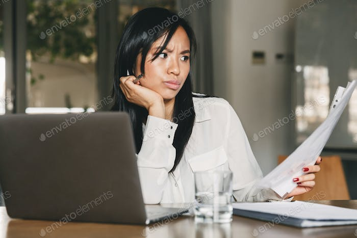 Photo of concentrated asian woman 20s wearing office clothing ho
