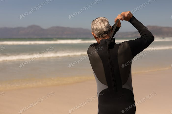 Rear view of senior male surfer wearing wet suit on the beach with mountains in the background