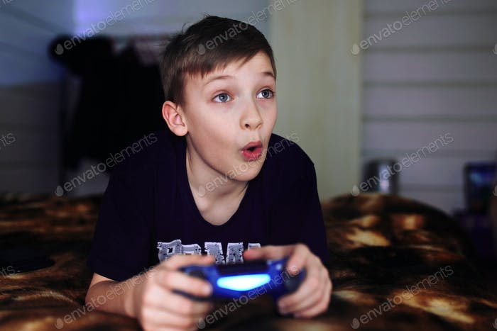 A teenager is sitting on the sofa and playing a video game.