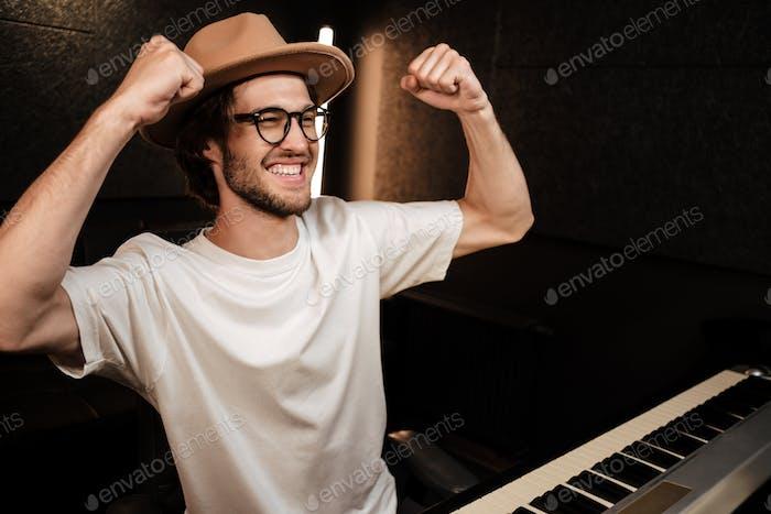 Junge Musiker hebt glücklich die Hände hoch zeigt gewinnen Geste arbeiten im Tonaufnahmestudio