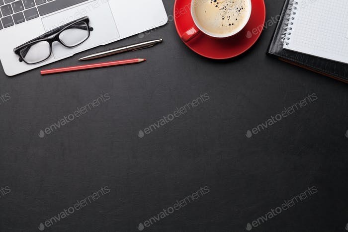 Office workplace table with coffee, supplies and computer