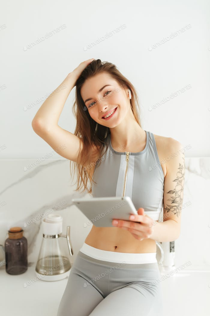 Beautiful smiling lady in sporty top on kitchen with tablet and earphones happily looking in camera