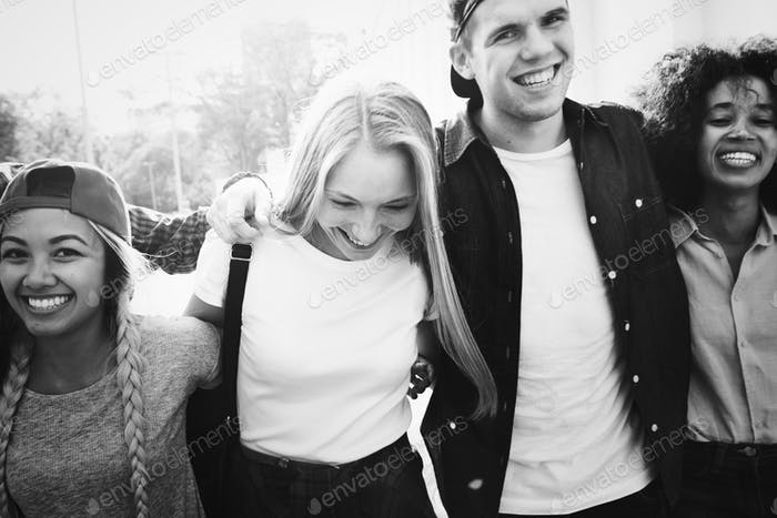 Smiling happy young adult friends arms around shoulder walking o