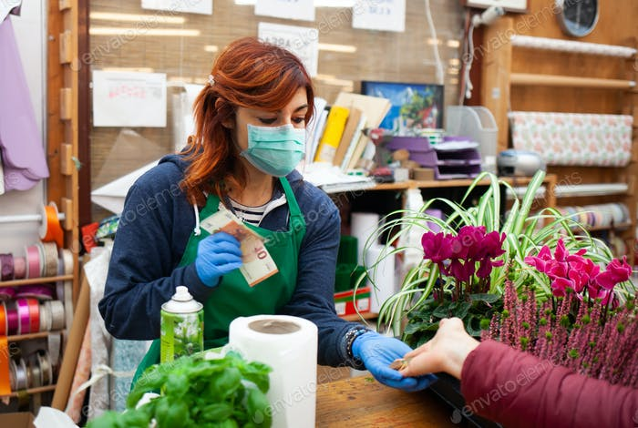 Florist receives a payment from a customer wearing a mask and gloves due to the coronavirus .