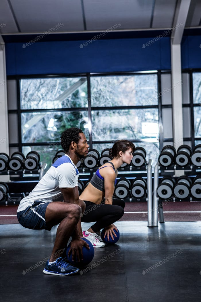 Fit couple exercising with medicine ball at gym