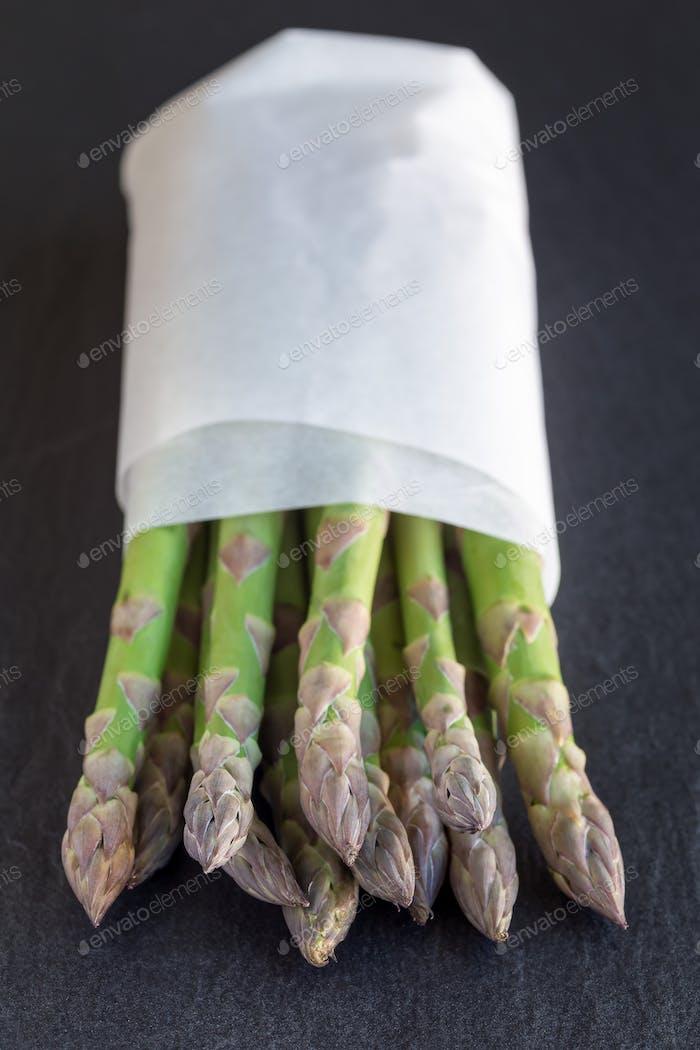 Bündel frischer grüner Spargel auf dunklem Schiefergrund, vertica