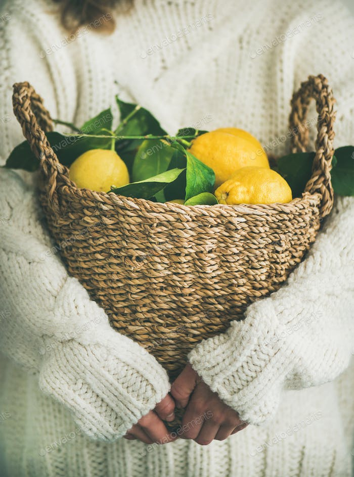 Woman in white woolen sweater holding basket of fresh lemons