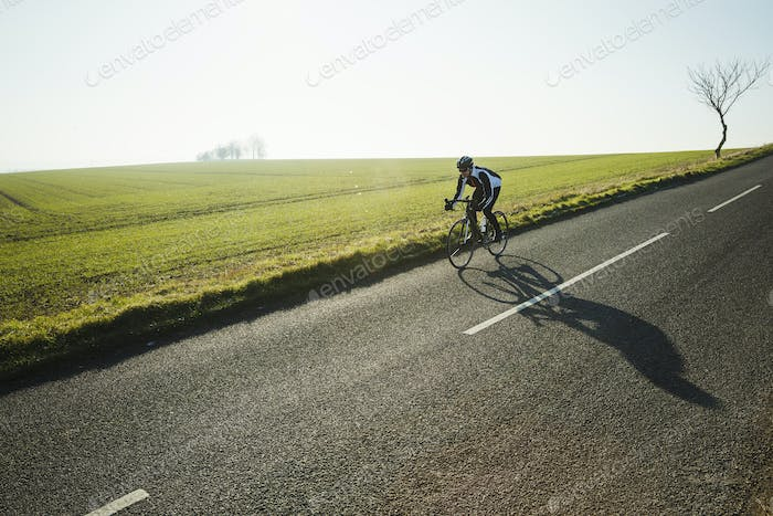 A cyclist riding along a country road on a clear sunny winter day.