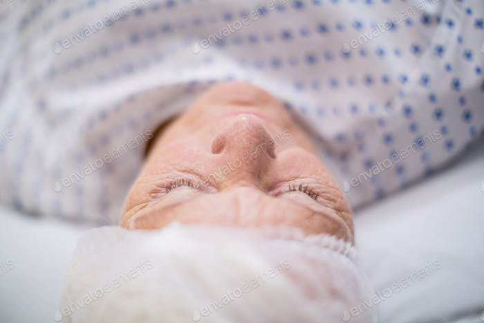 Senior woman patient sleeping on bed