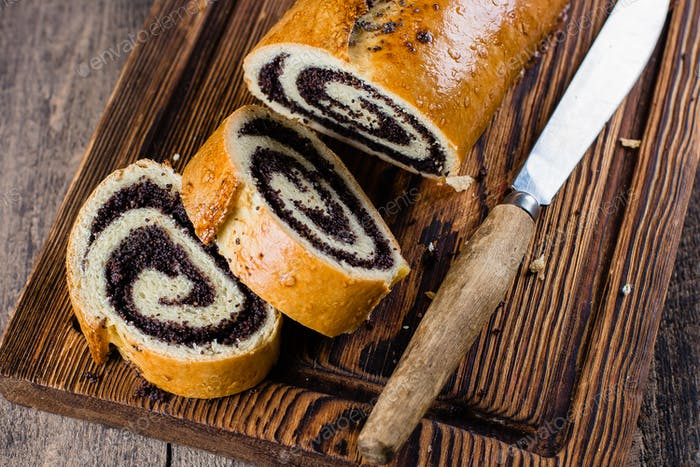 Homemade roll with poppy seeds on wooden board on wooden table background. Close up