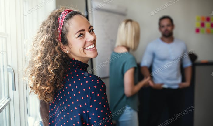 Smiling designer looking over her shoulder during a meeting
