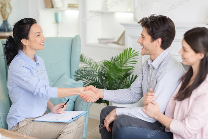 Professional psychologist and relieved couple handshaking after therapy