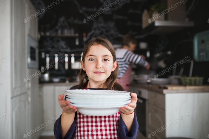 A small girl with grandmother helping in the kitchen.