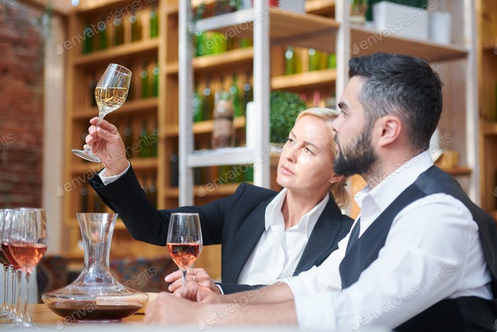Two professionals sitting by workplace while looking at sample of white wine