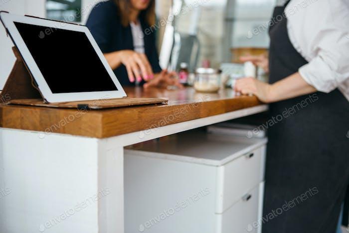 Pad on counter near two talking women