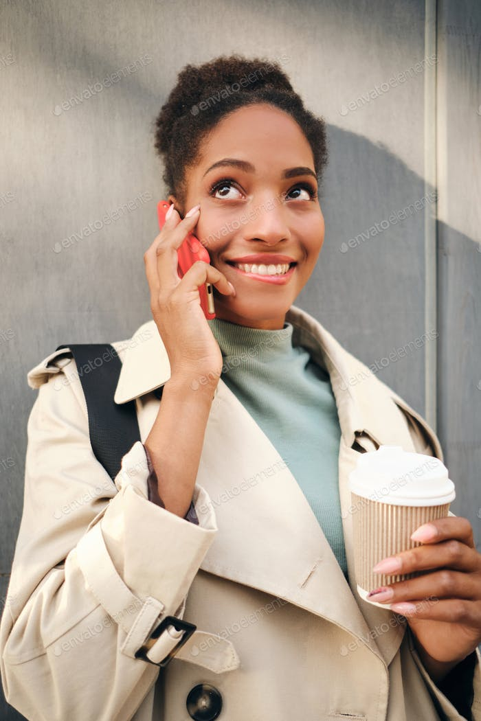 Flirty African American girl in stylish trench coat with coffee happily talking on cellphone outdoor