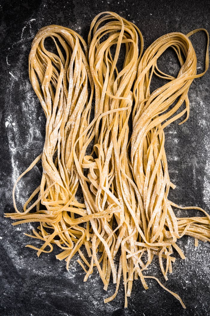 Raw uncooked taglietelle pasta, copyspace bacground
