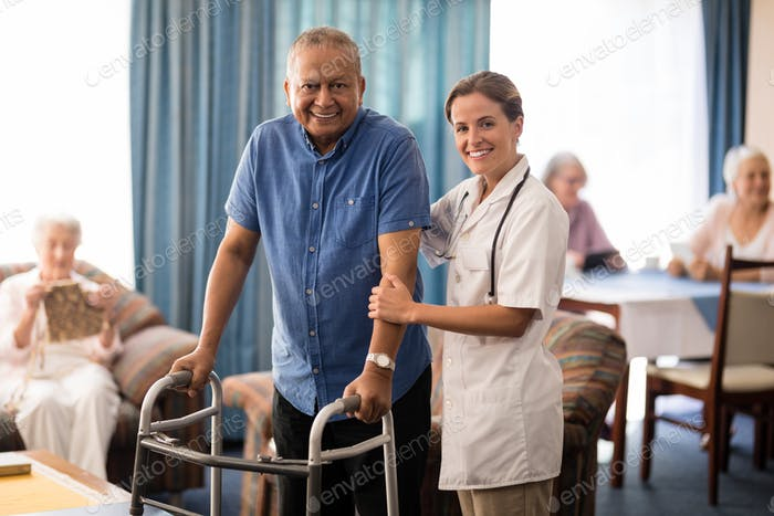 Portrait of smiling female doctor standing by senior man with walker