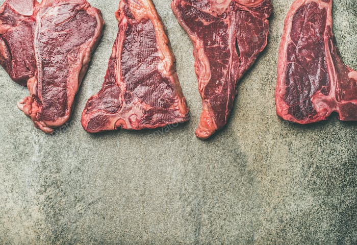 Flat-lay of fresh raw beef meat steaks over concrete background