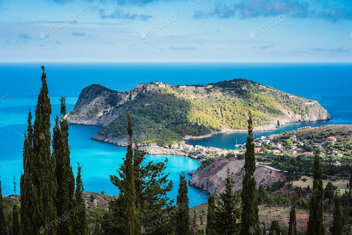 View to Assos village in sun light and beautiful blue sea. Cypress trees in foreground. Kefalonia