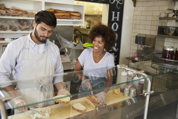 Gemischte Rennen Paar arbeiten hinter der Theke an einer Sandwich-Bar