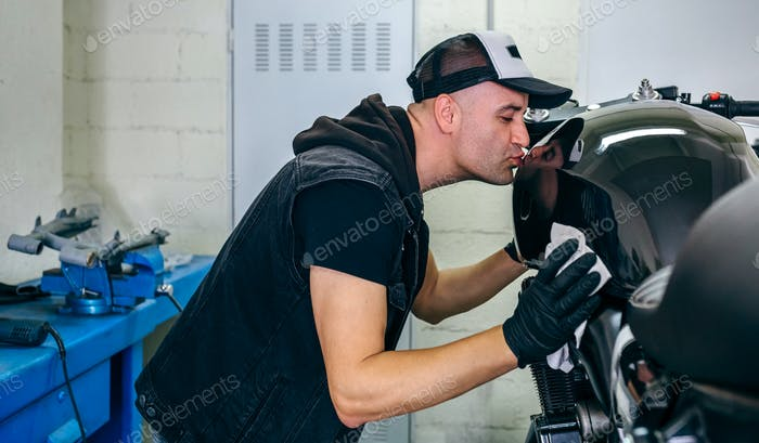 Mechanic kissing the motorbike