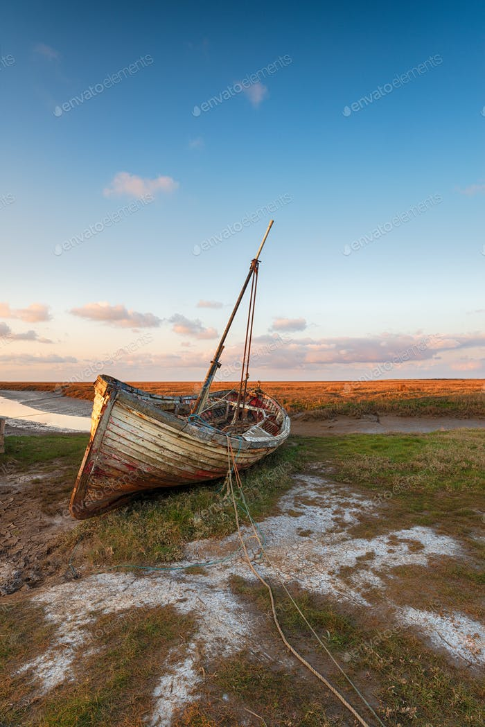 An old wooden fishing boat on the shore at Thornham harbour
