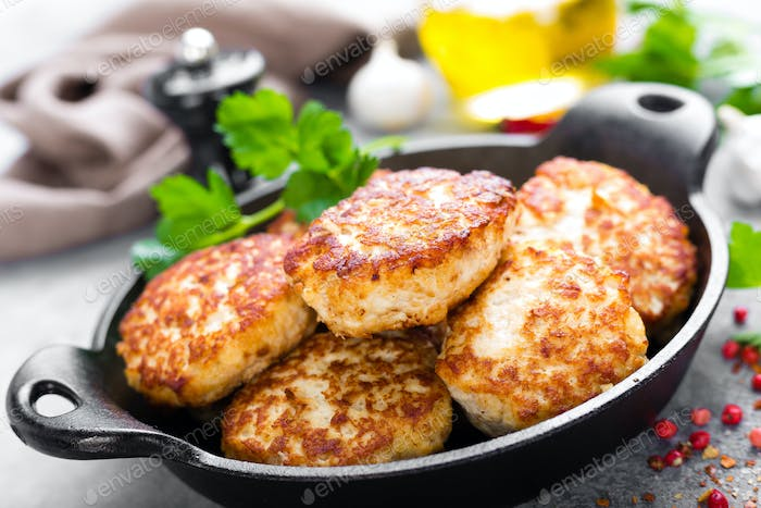 Cutlets. Fried cutlets in cast-iron pan on table