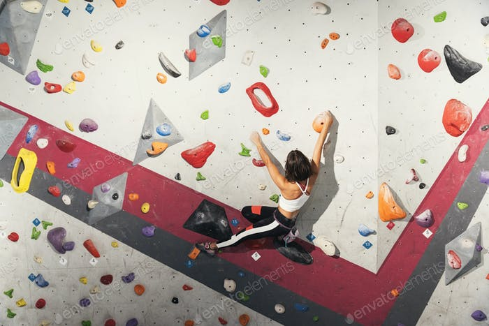 Woman practicing rock climbing on artificial wall indoors.