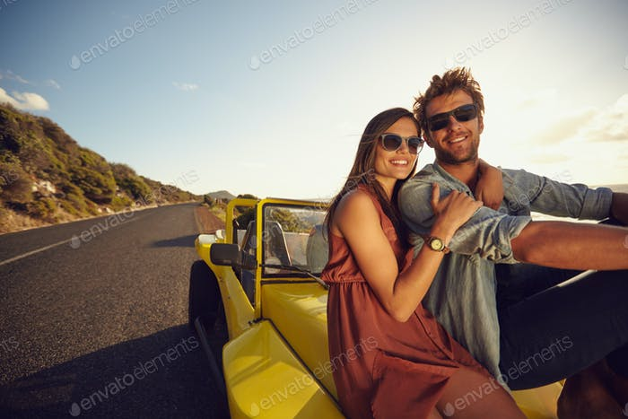 Attractive young couple sitting on the hood of their car