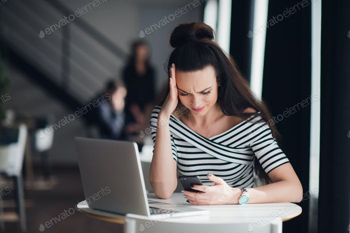 Portrait of stressed office young woman holding a cellphone in hands in a cafe, looking at the