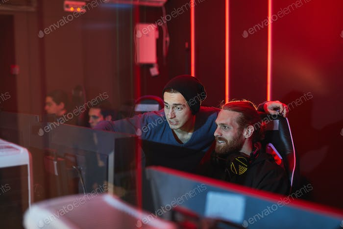 Friends playing computer game in pc game club