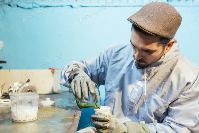 Man pouring container with green color